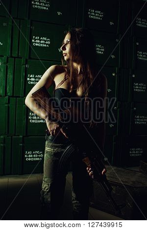 Pretty girl with ak-47 posing in a storage