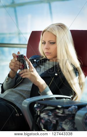 Young Pretty Blonde Woman With Mobile Phone Sitting In Arport
