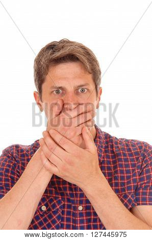 A young man in a closeup image holding his hands over his mouths looking scared isolated for white background.