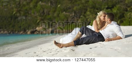 Beautiful Young Couple Kissing On Sunset Lying On Sand, Sunset Time. Panorama.