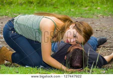 Young man lying down with medical emergency, woman sitting by his side checking for breath, outdoors environment.