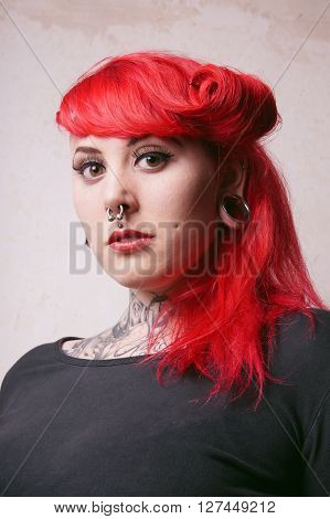 young alternative woman with facial piercings and tattoos