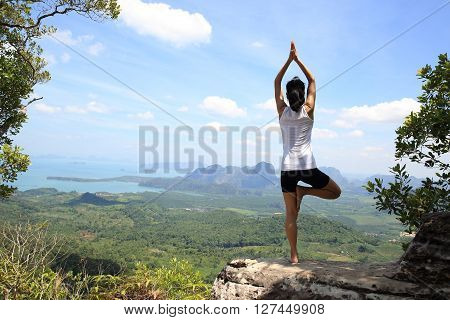 young fitness woman practice yoga at seaside mountain peak