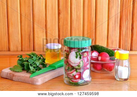 Vegetarian salad in a glass jar. Salad with fresh cucumbers and radishes. Trends in healthy eating. Set for cooking salad