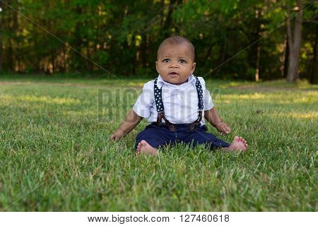 A 7 month old baby sitting in the grass