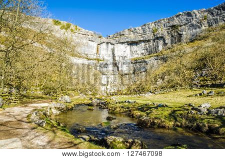 Limestone cliffs of Malham Cove in North Yorkshire, England on sunny day.