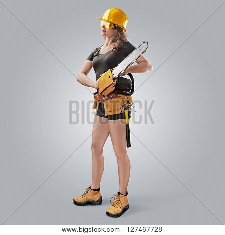 worker girl in a helmet with a chain saw on grey background