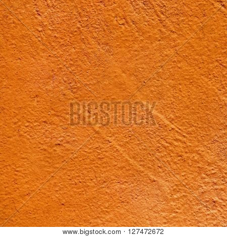 Orange painted texture. Orange colored background. Close-up of bright orange painted old textured wall.