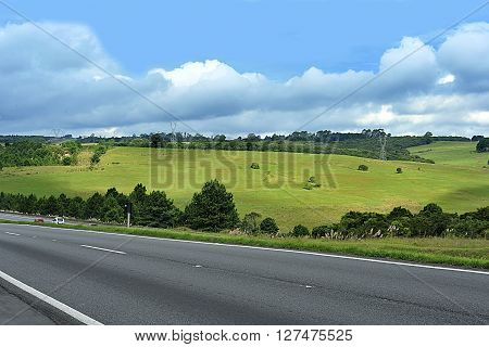 photo on the road beside field with mountains in blue and cloud sky.