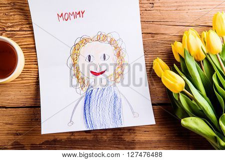 Mothers day composition. Childs drawing of her mother, bouqut of yellow tulips and cup of tea. Studio shot on wooden background.