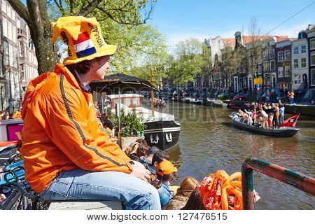 AMSTERDAM, NETHERLANDS on APRIL 26, 2015. City native tourist with orange color decoration watching celebrating Queen's Day or King's day, Dutch annual national holiday, in Amsterdam, Holland