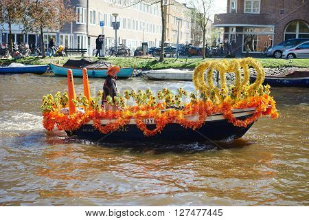 AMSTERDAM, NETHERLANDS on APRIL 26. City native sailing on crown decorated cruiseboat ship on river canal during Queen's Day or King's day, Dutch annual national holiday in Amsterdam, Holland