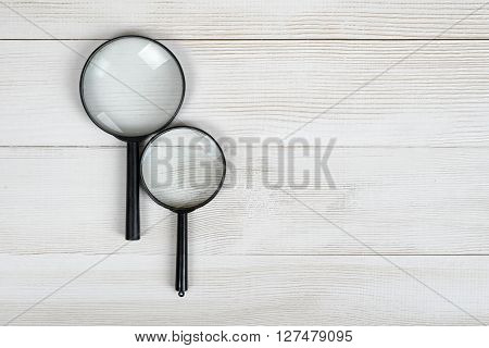Magnifying glasses lying on a wooden surface with open space in top view. Workplace of geologist, physician, archaeologist, banker, criminalist or jeweler. Optical system. Research and investigation. Deep scan.