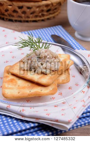 Appetizer of fish paste (forshmak) on crackers on a plate