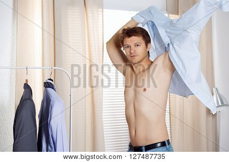 Handsome man putting on shirt standing near window at his room in morning. Preparing for some event or new workday. New opportunities dating wedding day or getting ready for job interview concept