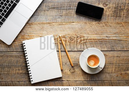 Working place at home on wooden table with laptop, notebook, phonel and cup of coffe