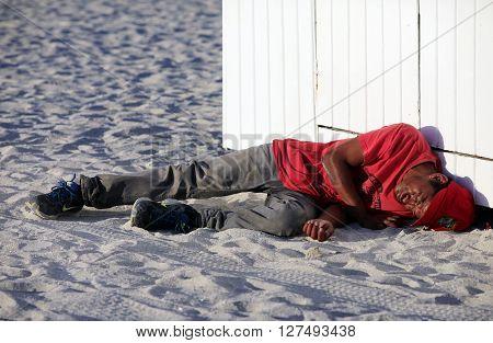 Miami Beach USA - May 5 2013: Sleeping homeless drunkard lying on the beach in Miami