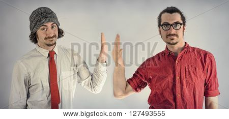 Twin adult men with beards high fiving each other