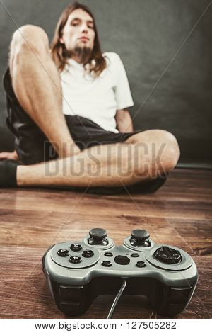 Addiction and dependency concept. Young man with pad joystick playing games. Male addicted to console playstation videogames.