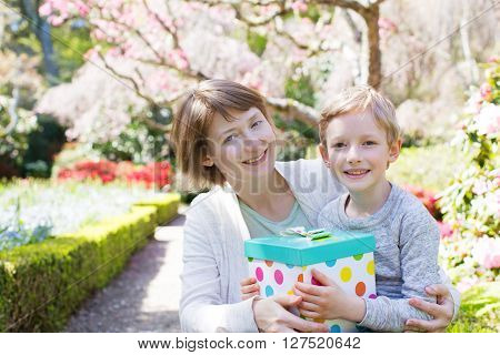 young beautiful mother and her little son giving her a gift for mother's day enjoying time together at spring time in the park