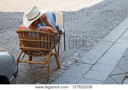 Naples Italy - August 9 2015: Illegal parking valet strong man sitting on the roadside for car place reservation