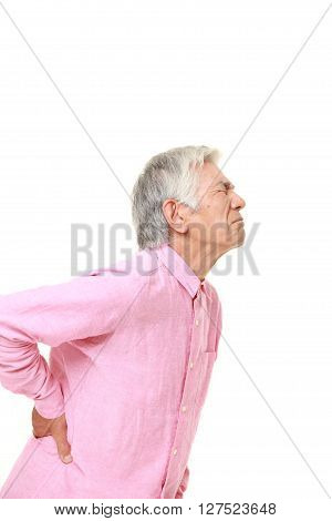 studio shot of senior Japanese man suffers from lumbago on white background