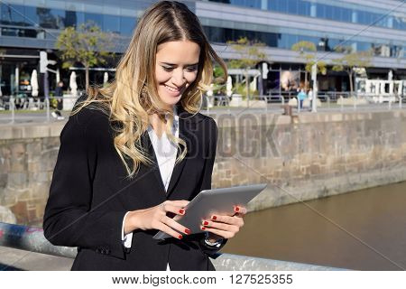 Succesful business woman working on a tablet outside her office.
