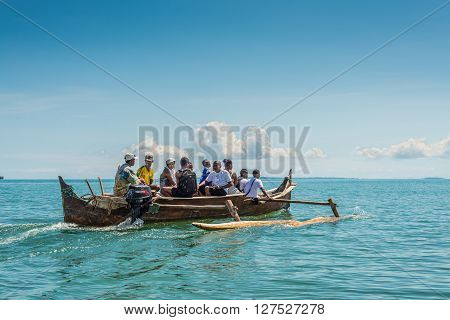 Ambatozavavy Nosy Be Madagascar - December 19 2015: Tourists with a guide crossing the inlets by outrigger canoe near the Ambatozavavy village in Nosy Be island north of Madagascar.