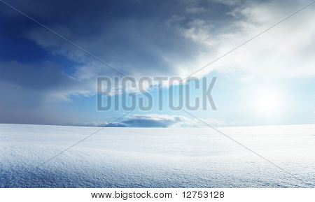 field of snow and cloudy sky