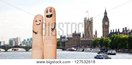 family, couple, travel, tourism and body parts concept - close up of two fingers with smiley faces over london city with big ben clock tower and thames river background