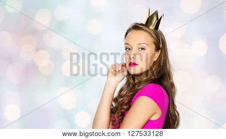 people, holidays and fashion concept - young woman or teen girl in pink dress and princess crown over holidays lights background