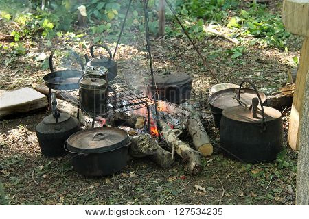 A Collection of Pots and Pans Around a Wood Fire.