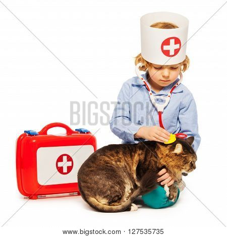 Little boy playing doctor veterinarian with a cat, isolated on white background