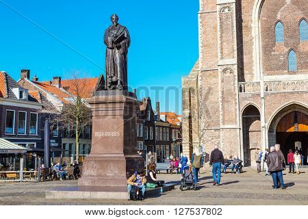 Delft, Netherlands - April 8, 2016: Colorful street view with statue of Hugo Grotius, Nieuwe Kerk or New Church entrance, traditional dutch houses on the square, people walking in downtown of popular Holland destination