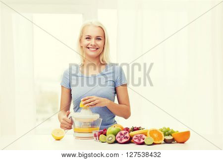 healthy eating, vegetarian food, diet, detox and people concept - smiling woman with squeezer squeezing fruit juice at home