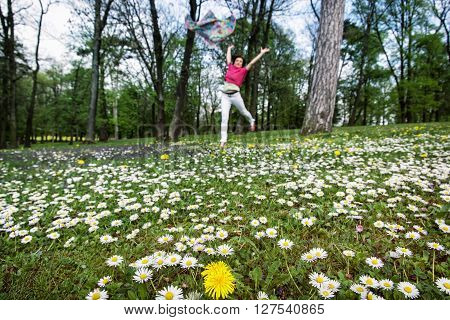 Young woman with silk scarf is jumping on the meadow full of ox-eye daisies and dandelions. Beauty fashion and nature. Big fun. Crazy woman. Woman in love. Natural beauty.