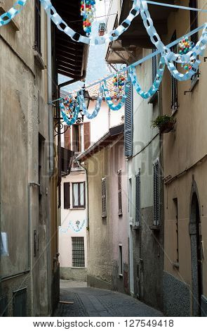 colorful bunting ribbons hanging in a narrow and quaint Italian street