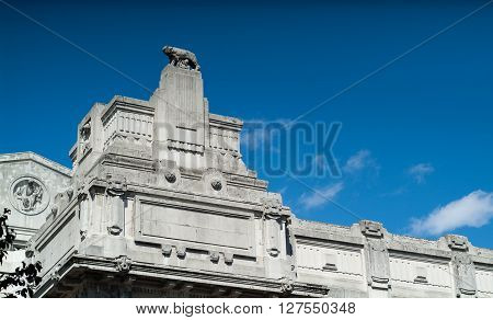 Milan, Italy - September 5th 2015: closeup photo of the facade of the Milano Centrale railway station against blue sky. The wolf sculpture references the legend of Romulus and Remus the founders of Rome.