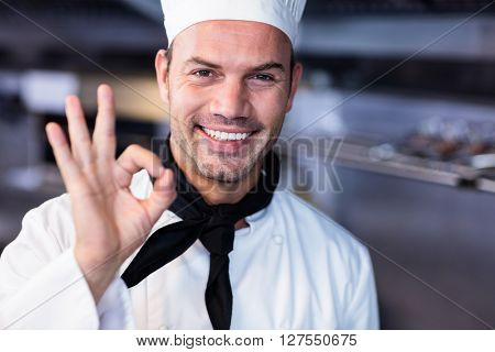 Portrait of happy chef making ok sign in commercial kitchen