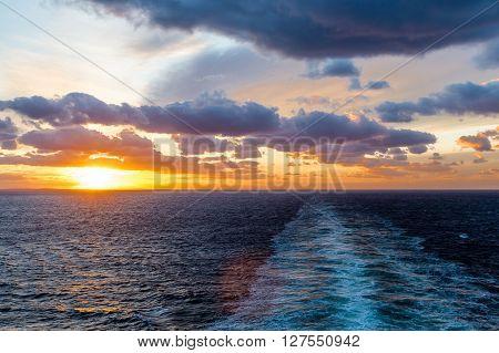 A beautiful orange sunset at sea in wake of ship