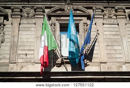 Milan, Italy - September 5th 2015: three flags (Italy EU and presumably Unesco) photographed in central Milan on September 5th 2015.