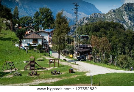 Piani d'Erna Italy - September 7th 2015: a group of countryside houses and a wooden playground photographed at Piani d'Erna (part of the Alps) near Lake Como in Italy