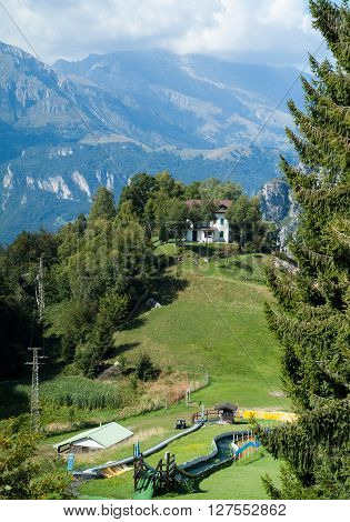 a white house and a playground on top of a hill at Piani d'Erna (part of the Alps) near Lake Como in Italy