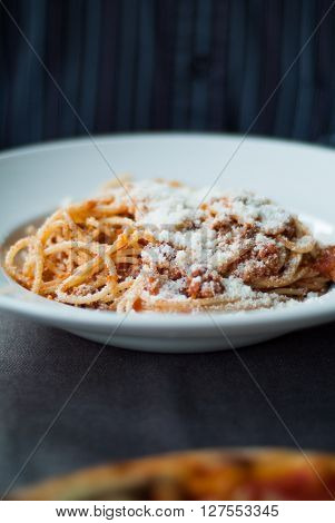 closeup of a plate of spaghetti bolognese with parmesan photographed at an Italian restaurant