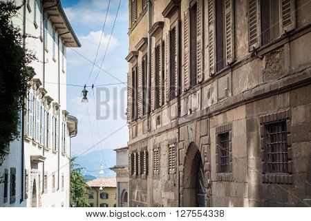 a piece of sky showing in-between two traditional buildings in Bergamo a town near Lake Como