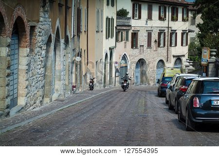 Bergamo, Italy - September 9th 2015: a man riding a motorbike on a quaint street in the upper part of Bergamo a town near Lake Como.