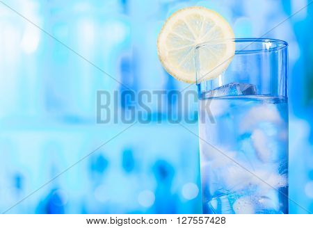 One glass of water with ice cubes decorated by lemon slice standing at the bar