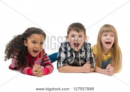 three funny children lying on the floor with open mouths isolated on white background
