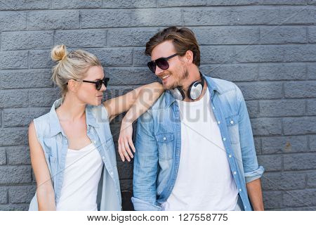Young couple in sunglasses leaning against wall