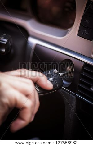 Color image of a hand inserting the ignition key of a car.